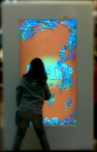 Kid playing with a life size outdoor display in a mall